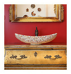 Florentine painted vessel sink in a red and gold bathroom